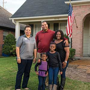 A family poses in front of their new home