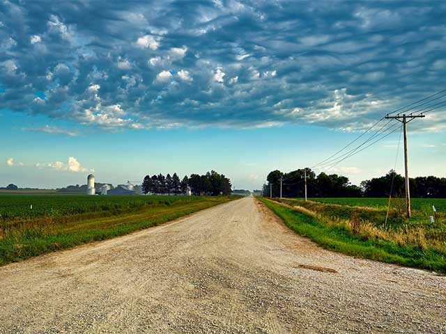 Country road with a silo in the distance
